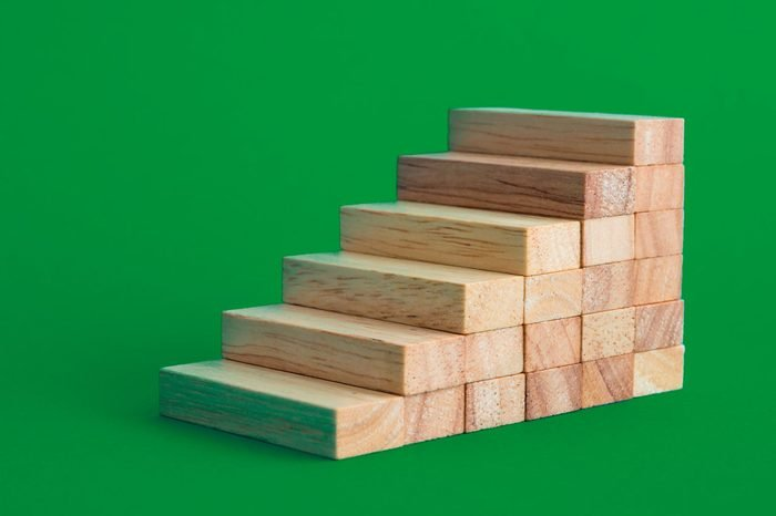 Wood block stack as stair step on blue background with copy space. Abstract business goal, target, growth or success plan concept.