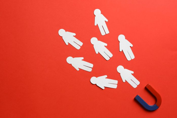 Magnet attracting paper people on red background, flat lay. Space for text