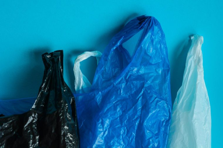 Black, blue and white plastic bags on blue background. Representation of plastic pollution concept