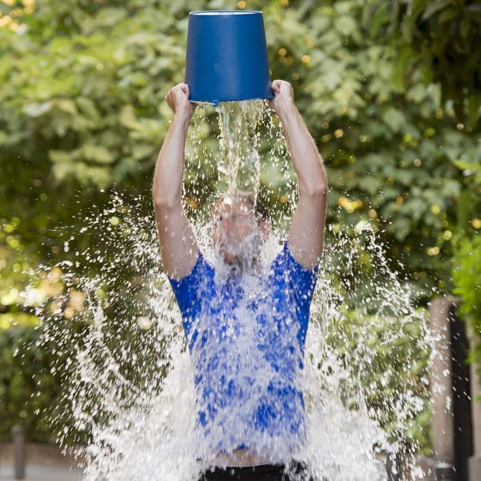 young man pouring ice water bucket on his head getting wet outdoors in internet viral media network challenge campaign to support degenerative sclerosis and neuronal disease and disorder ; Shutterstock ID 214403830; Job (TFH, TOH, RD, BNB, CWM, CM): -