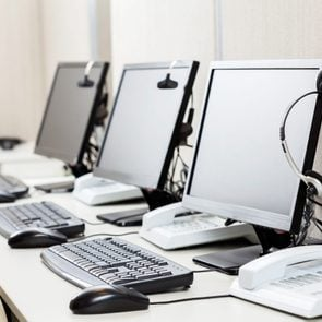 Row of computers with headphones on desk at call center