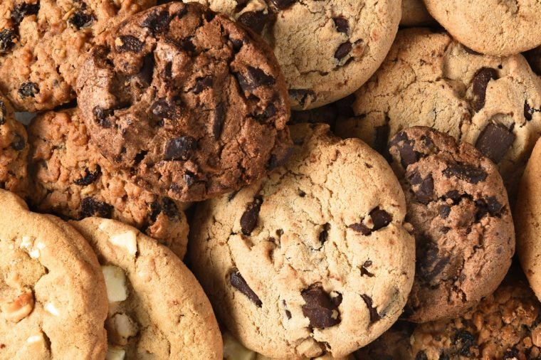 Closeup of a group of assorted cookies. Chocolate chip, oatmeal raisin, white chocolate fill the frame.