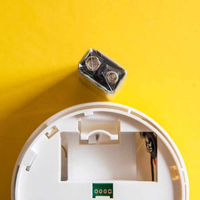 White smoke detector with nine volt battery on yellow background. A smoke detector is a device that senses smoke, typically as an indicator of fire.