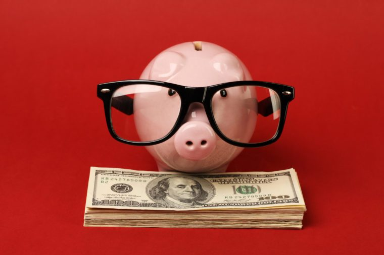 Piggy bank with black spectacle frame of glasses standing on stack of money american hundred dollar bills on red background