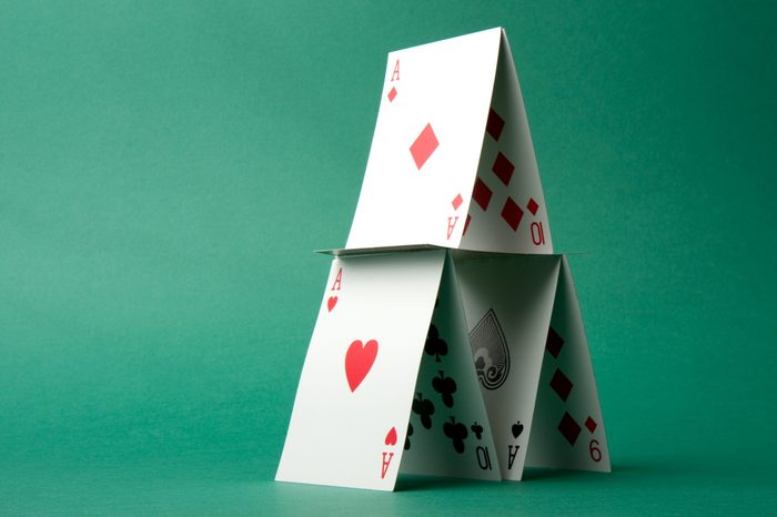 A house of cards on a green background.