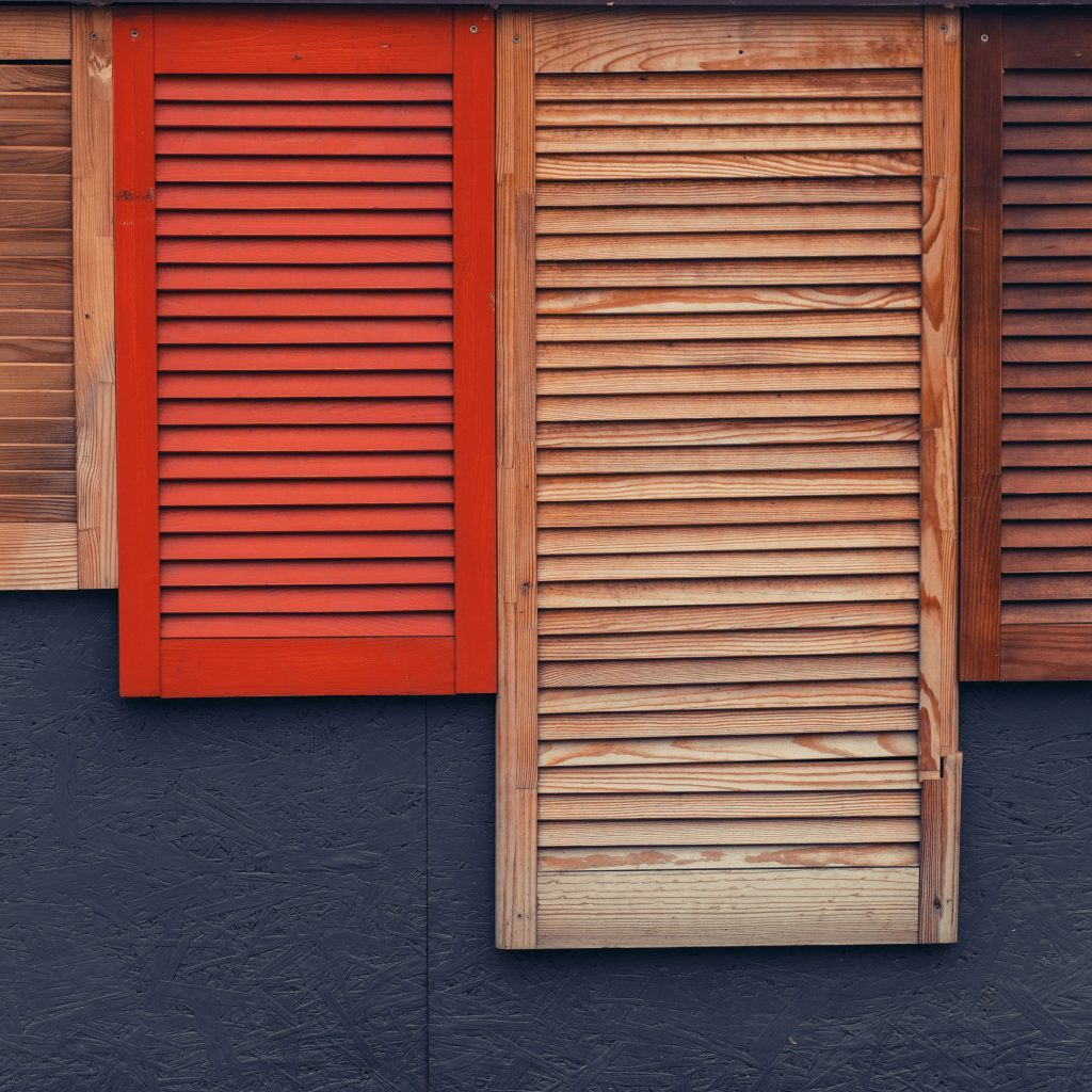 A bunch of wooden window shutters pattern on grey wall. Restaurant cafe warehouse decor. Naked worn wooden and plain painted shutters. Hipster loft wallpaper.