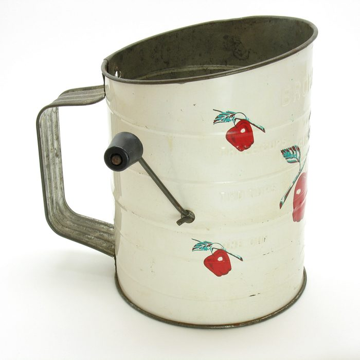 An antique tin flour sifter. A white painted tin flour sifter decorated with tiny red apples. Old hand crank design.