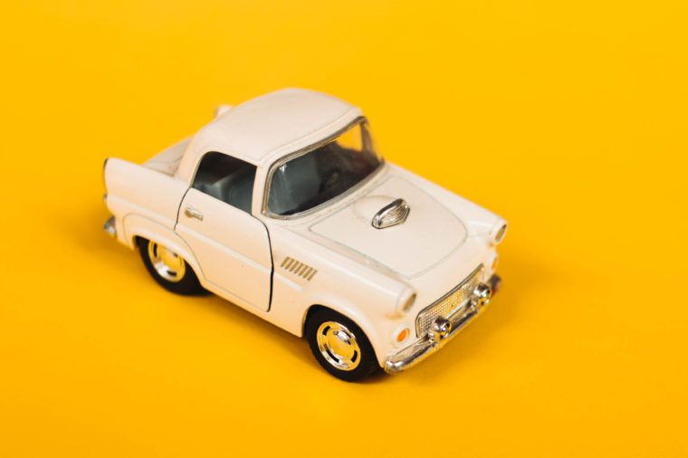 Classic fifties scale model toy car from front view with yellow background