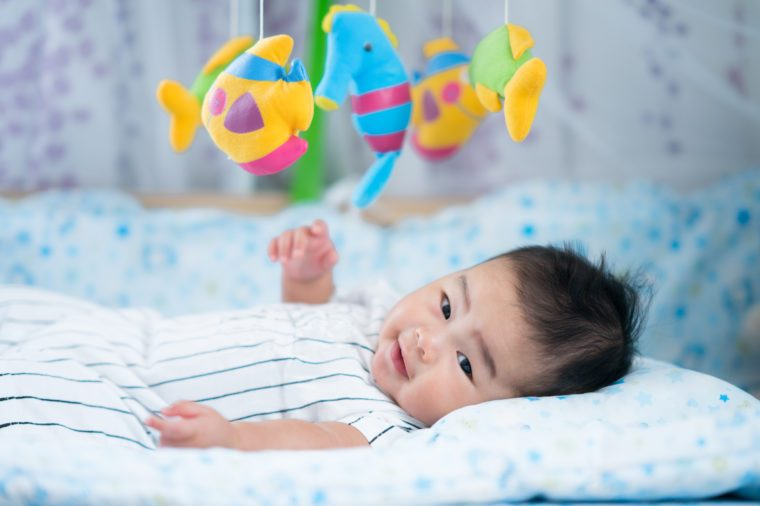 Asian newborn baby smile in a bed with fish and animal mobile. for mom, mother, family concept