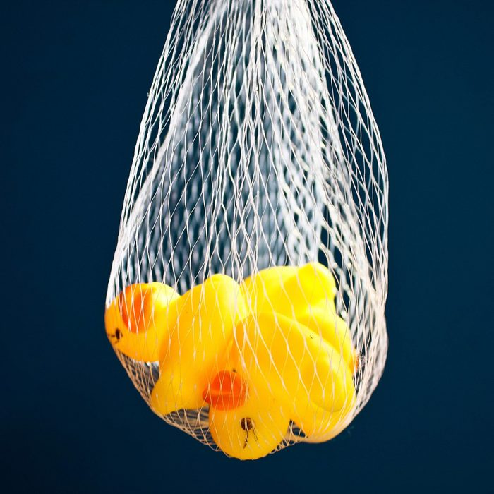 Duck dolls made of rubber in mesh bag.On a blue background