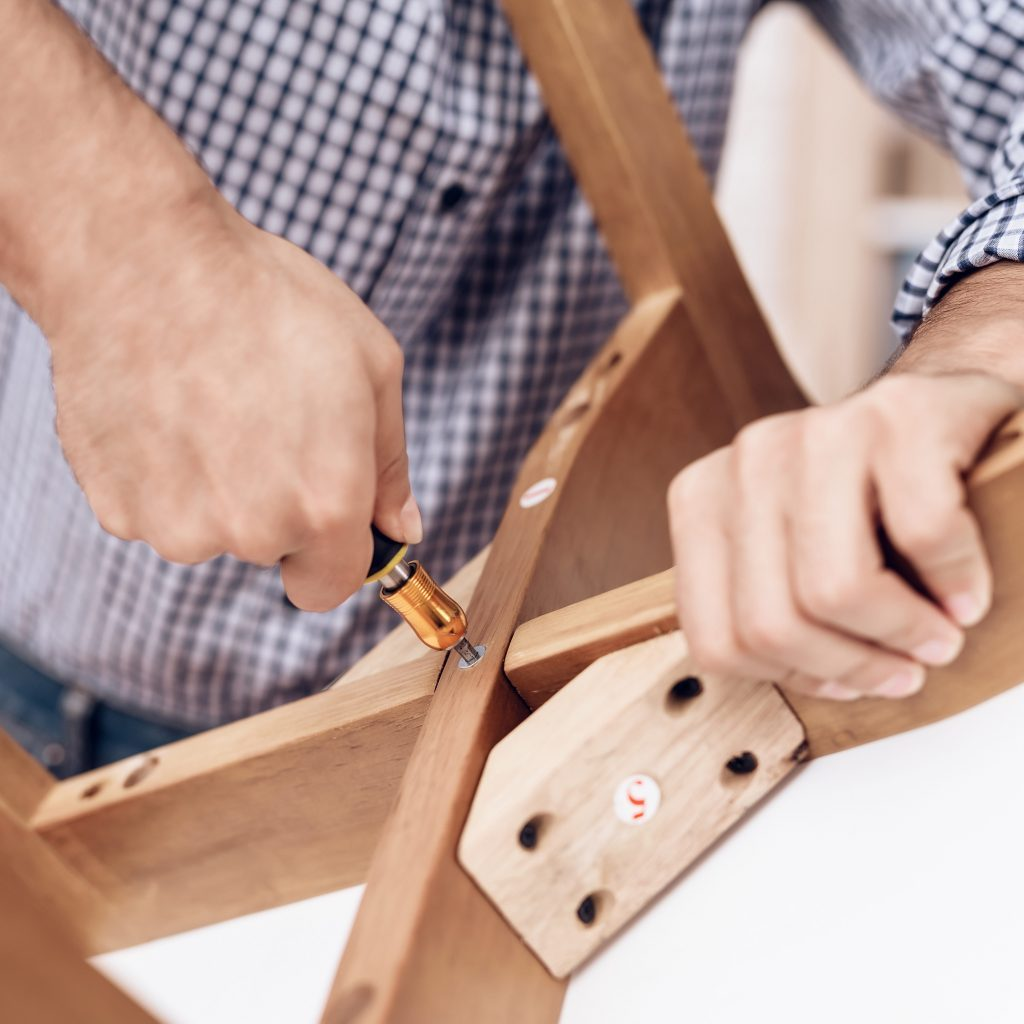 The man handyman is engaged in assembling the chair. The repairman is engaged in mending the chair.
