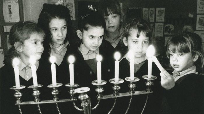 school girls lighting the menorah