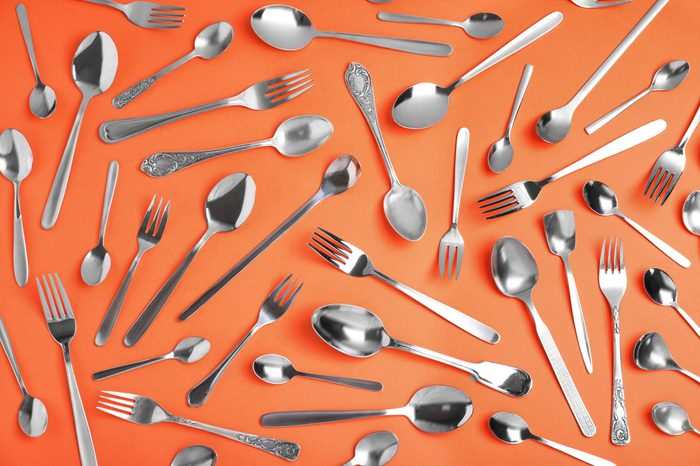 Set of new silver cutlery on coral background, flat lay