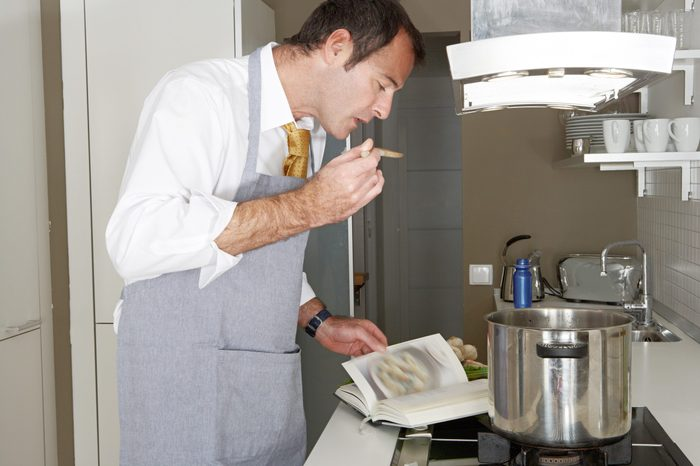 Businessman following the instructions in a cooking book to cook food at home, tasting it with a wooden spoon.
