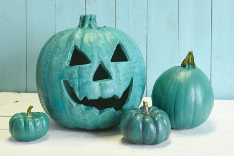 Teal pumpkins in a Halloween still life indicating that both allergy safe non food treats as well as candies are available to trick and treaters.