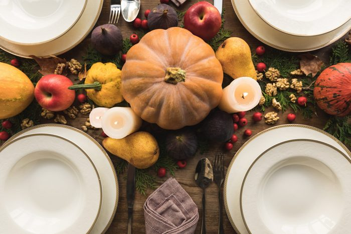 top view of cutlery, candles and autumn decor on served table