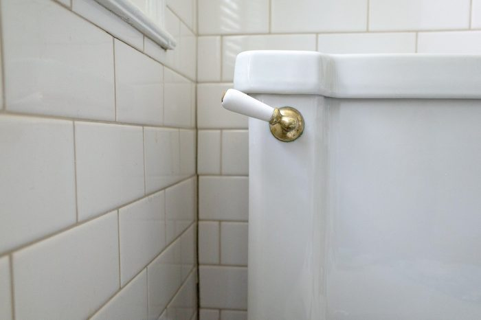 An Art Deco period toilet with porcelain and brass flush handle and vintage subway tiles