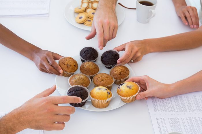 Hungry workers grabbing muffins in the office