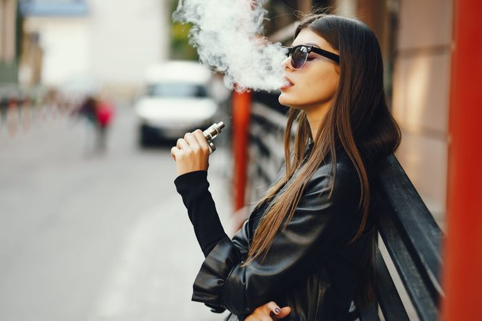 stylish girl smoking an e-cigarette as she is walking through the city
