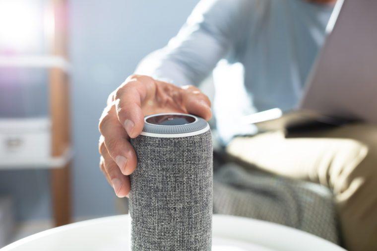 Man Adjusting Volume On Wireless Speaker At Home