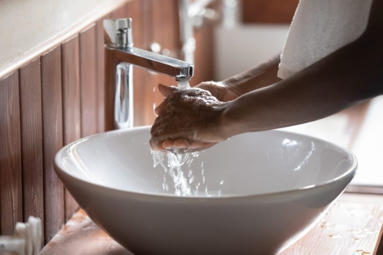 Crop close up of african American man clean hands in pure water from tap or faucet, perform morning cleanup routine at home, biracial male wash in modern design sink after having shower in bathroom