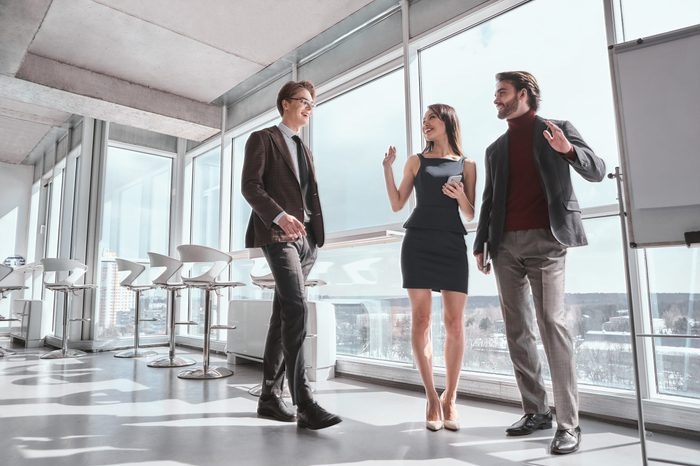 Businessmen and businesswoman at office working together standing man and woman greeting coming collegue smiling joyful