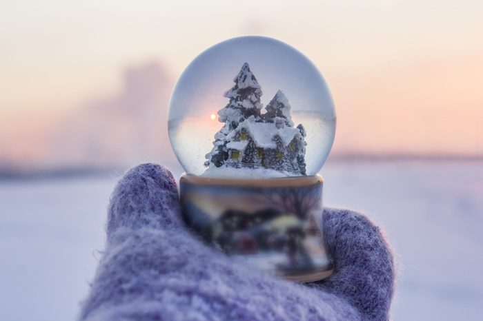 Girl in knitted mittens holding glass ball with firtrees, house and artificial snow with winter landscape at the background
