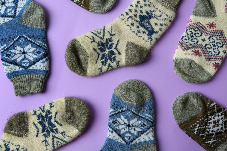 Different knitted socks on violet background, flat lay. Winter clothes