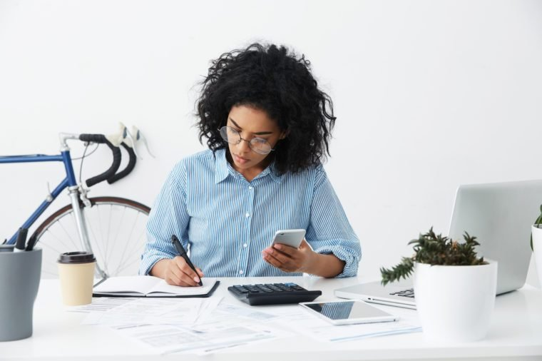 Concentrated focused Afro American female freelancer holding phone in one hand and making notes with pen in other while planning budget and calculating bills, sitting at desk with papers and gadgets
