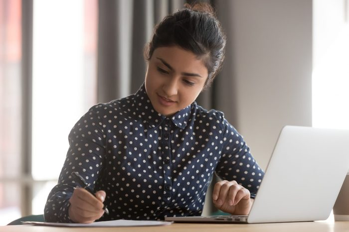 Young indian business woman student working studying online with laptop making notes sit at office desk, focused hindu female professional preparing report doing paperwork writing essay at workplace