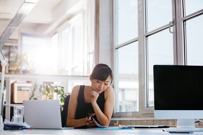 Shot of beautiful young woman sitting at her work desk going through some documents. Asian businesswoman working in modern office.