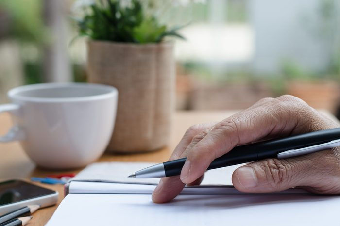 Man's hand holding a pen on paper notebook on table in relax position.