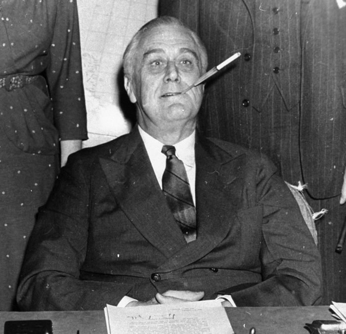 """Mandatory Credit: Photo by Uncredited/AP/Shutterstock (6010767a) President Franklin D. Roosevelt poses for photographers with a cigarette in his mouth as he started his 11th year in the White House. He said, """"Let's make one this way, boys."""" On Jan. 11, 1964, U.S. Surgeon General Luther Terry released an emphatic and authoritative report that said smoking causes illness and death - and the government should do something about it Smoking Report Anniversary, Washington, USA"""