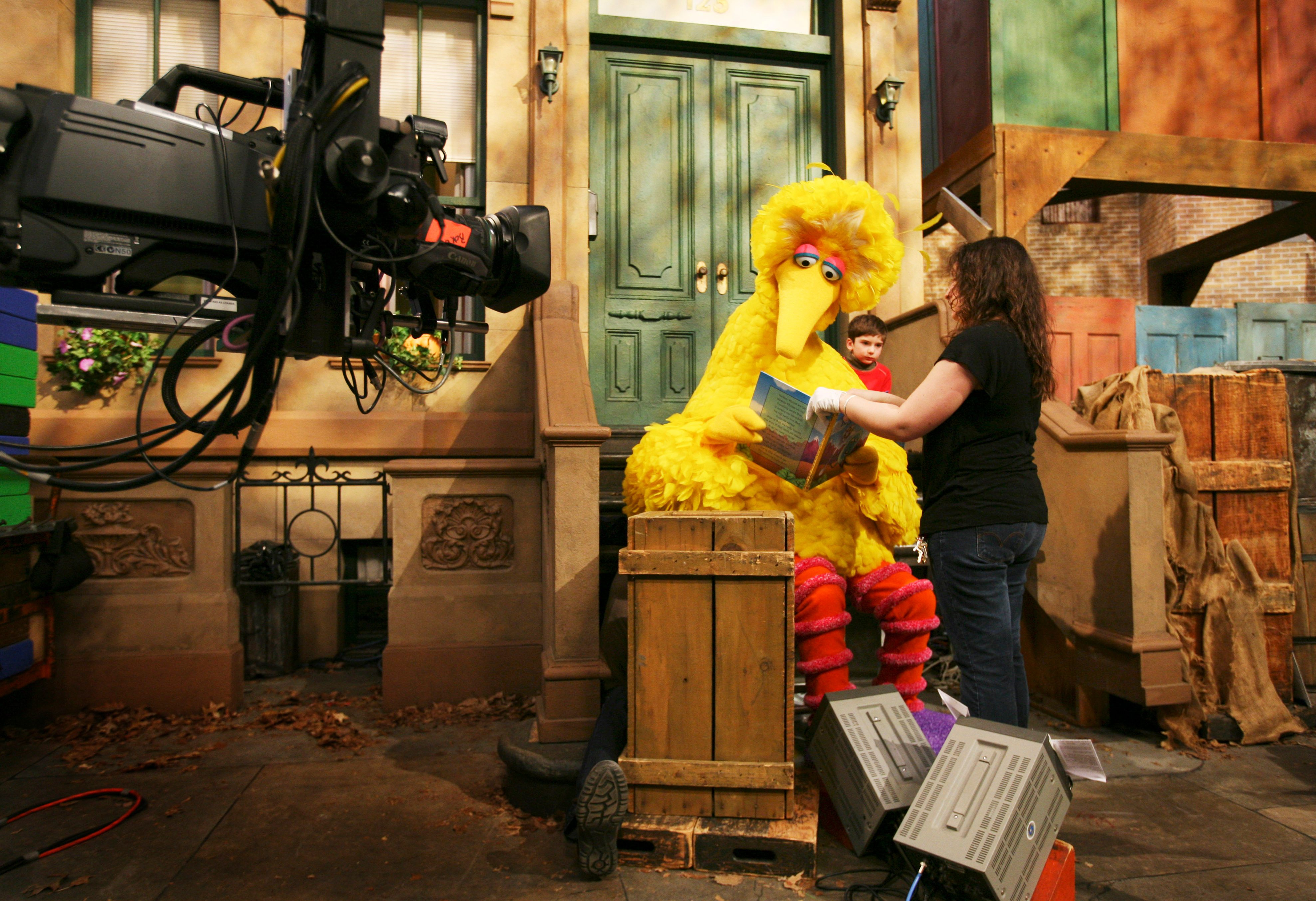 """Mandatory Credit: Photo by Mark Lennihan/AP/Shutterstock (6359732b) Caroll Spinney, Big Bird Michelle Hickey, a Muppet wrangler adjusts a book for Big Bird, voiced by Carroll Spinney, so he can read to Connor Scott during a taping of Sesame Street in New York. Spinney drops his fine-feathered obscurity (and emerges from his garbage-can fortress as Oscar the Grouch) for an enchanting film portrait, """"I Am Big Bird: The Caroll Spinney Story,"""" which celebrates the """"Sesame Street"""" puppet master who, at age 81, continues to breathe life into a pair of the world's best-loved personalities Film I Am Big Bird-Spinney, New York, USA"""