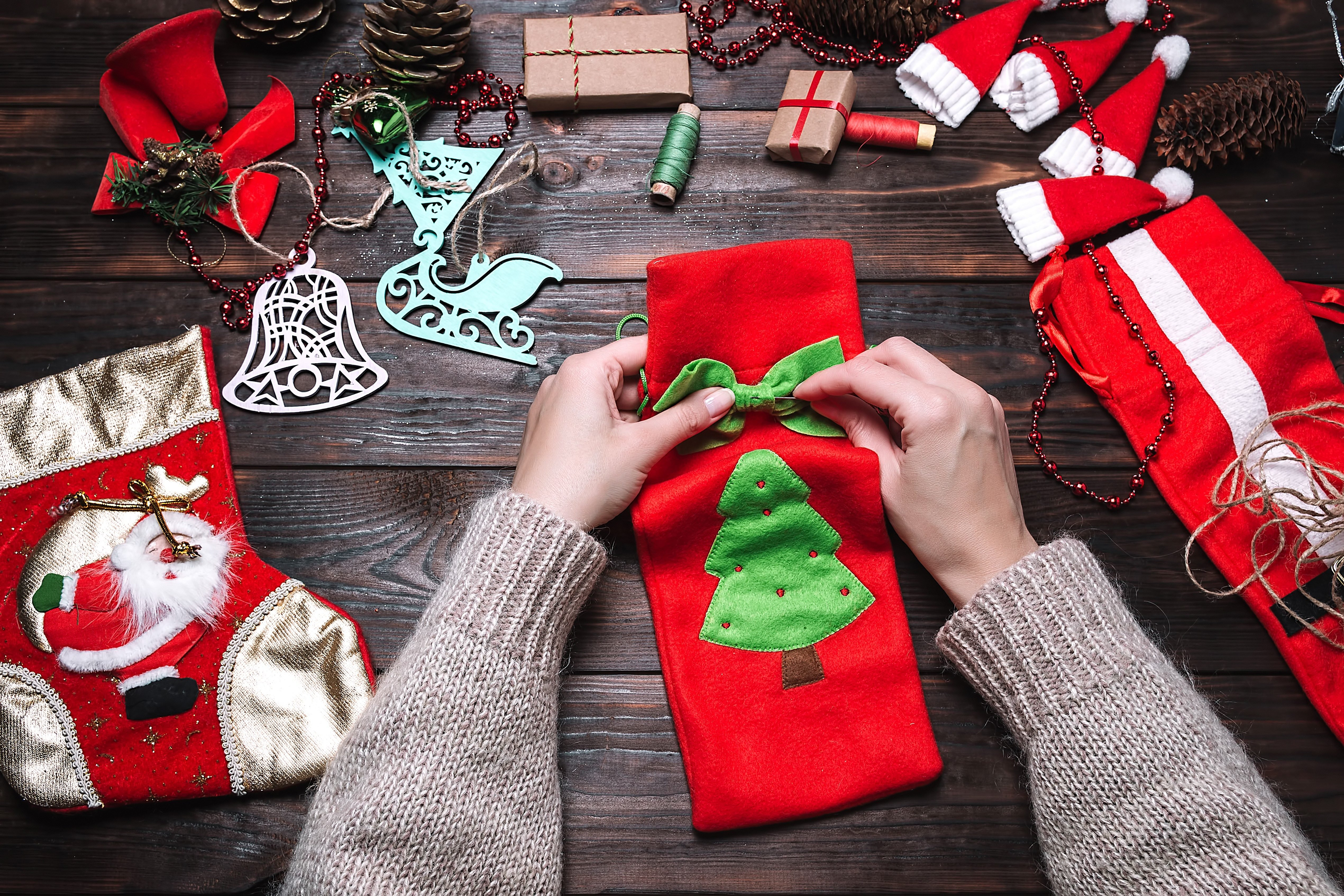 Girl makes Christmas gifts on a dark wooden table. Christmas decorations.