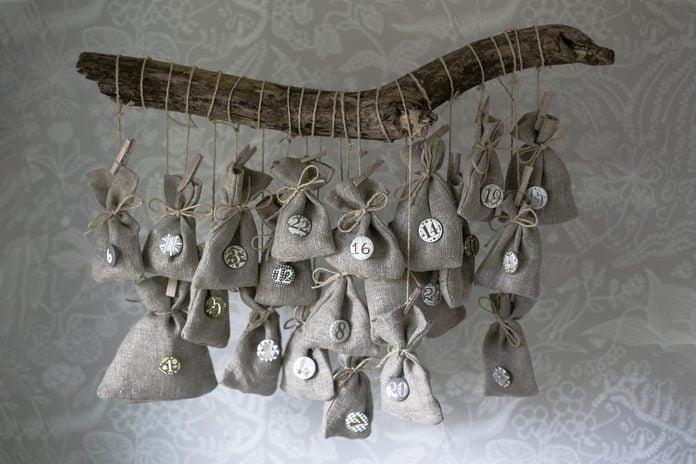 Homemade Christmas calendar Scandinavian style. Small linen bags hanging on a branch.