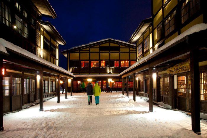 Night scene, two skiers walk through Niseko village in japan