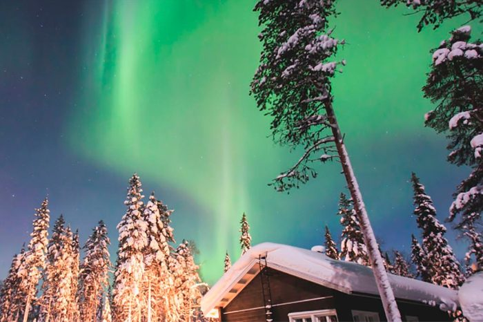 Auroroa Borealis over snowy trees and cabin in Finnish Lapland