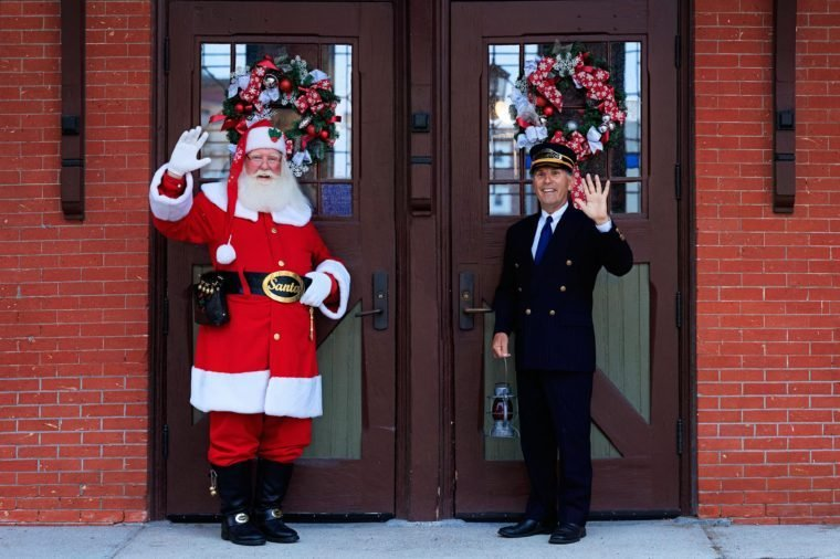 santa and the train conductor of the polar express wave to the camera