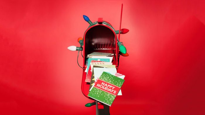 red mailbox open with christmas cards on red background