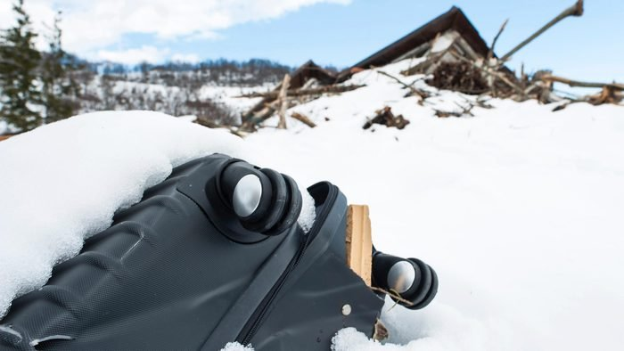Wheels of a suitcase stick out of a snowbank with a fallen building in the background