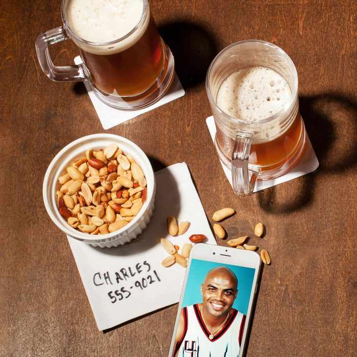 still life on wood. two mugs of beer, peanuts, cocktail napkin, phone showing charles barkley in a basketball uniform