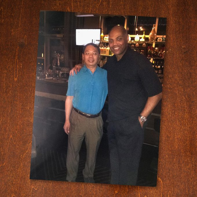 Charles Barkley poses with Lin Wang at the bar where they met.