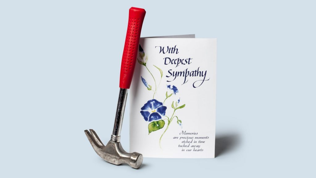 still life: hammer with a sympathy card on blue