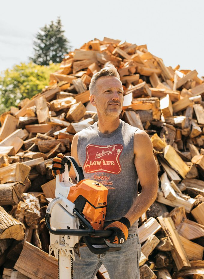 Shane McDaniel stands with his chainsaw in front of a large pile of cut wood