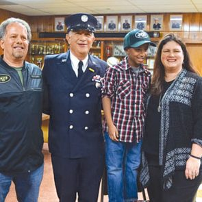 Pete DiPinto (second from the left) stands with Janice Esposito (far right) as he is honored at the fire house.