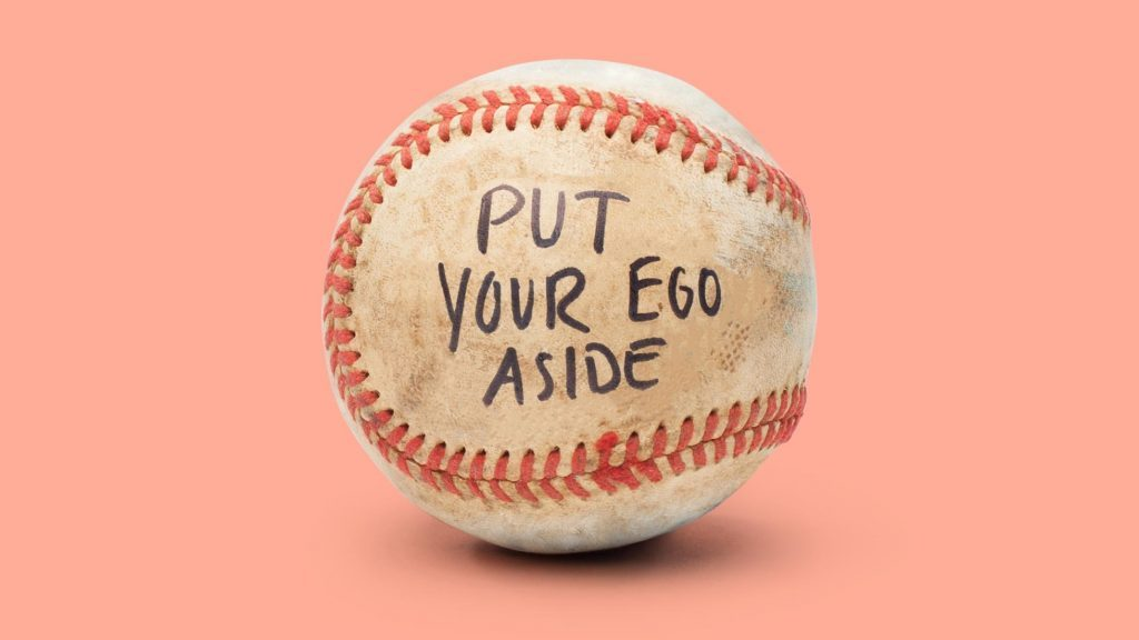"baseball on light red background. on the ball it reads, ""put your ego aside"""