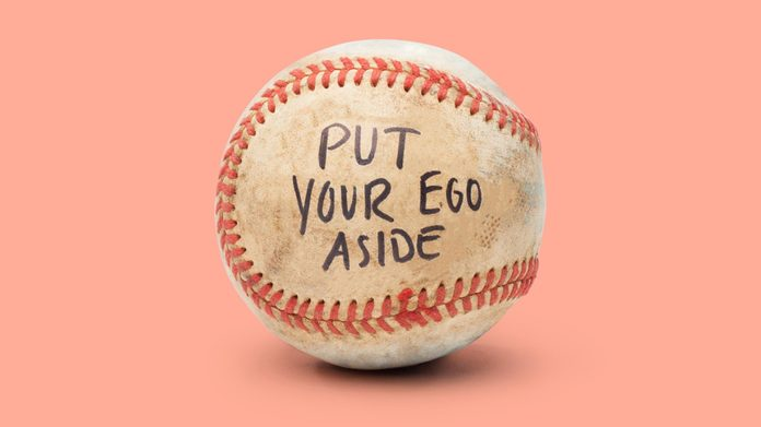 """baseball on light red background. on the ball it reads, """"put your ego aside"""""""