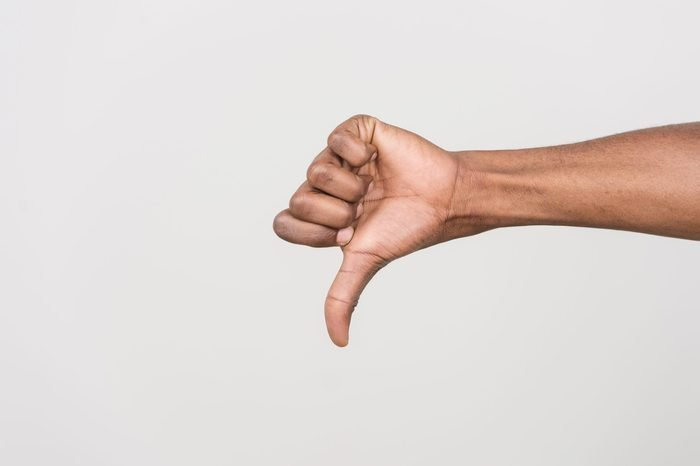 Thumb down hand signs isolated on white. black man hand gesturing with hand on white