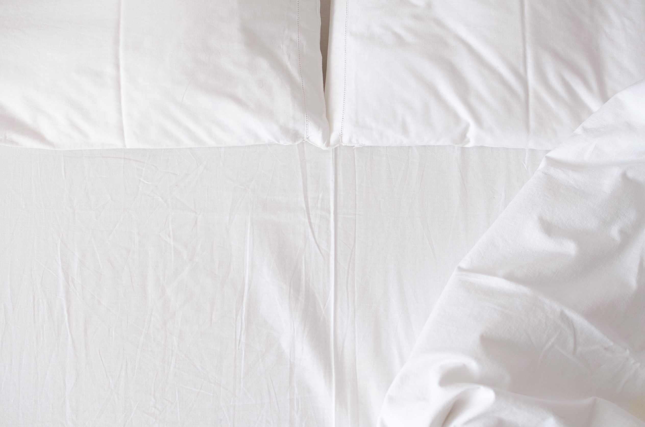 White bedding sheet, blanket and pillows in the hotel room. Rest, sleeping, comfort concept. Top view. Copy space.